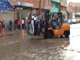 People Crossing Flooded Street In A Forklift