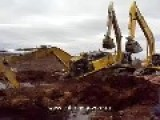 2 Diggers Pulling Out A 3rd Digger From A Muddy Hole