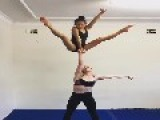 Two Gymnasts Do Balance Trick While Standing