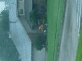 Man Mows Lawn During Storm