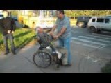 Old Con Man In Wheelchair Works A Crosswalk