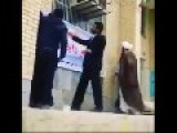 Stupid Mullah Inspecting Some Posters Falls On His Ass
