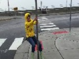 Woman Holds Onto Street Sign During Hurricane Winds