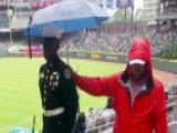 Baseball Fan Holds An Umbrella Over A JROTC Cadet