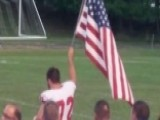 High School Football Player Raises American Flag At Game