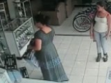 Woman Caught On Surveillance Tape Stealing TV Under Dress