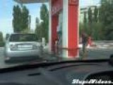 Two Women Struggle With Gas Pump